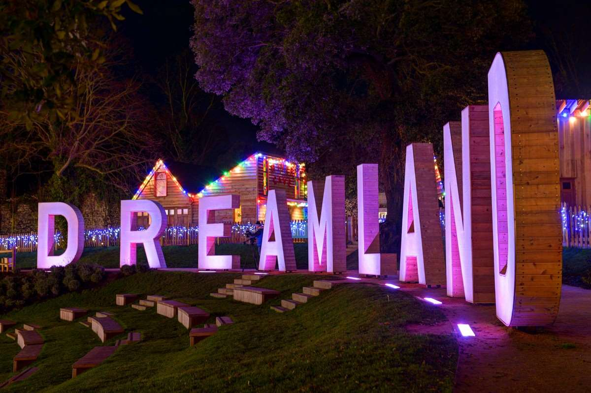 Santa's grotto can be seen lit up behind the Dreamland sign